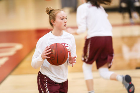 Senior guard Anna Harvey warms up before a game.